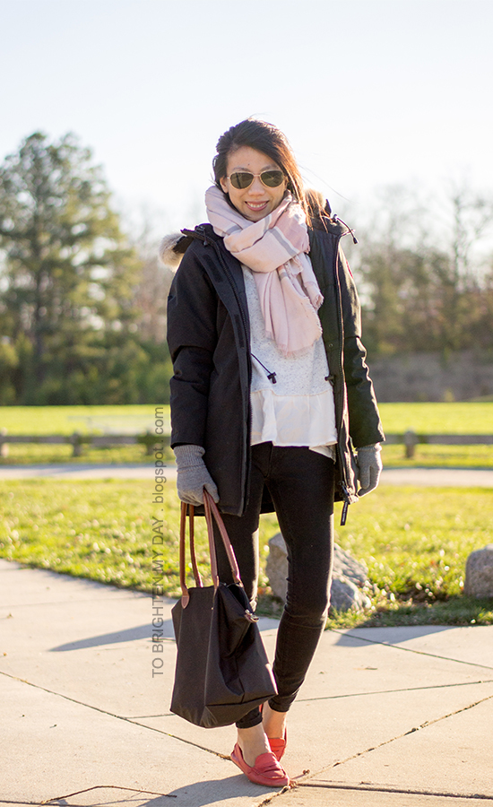 pink plaid blanket scarf, black parka, gray sweater with ruffles, red loafers