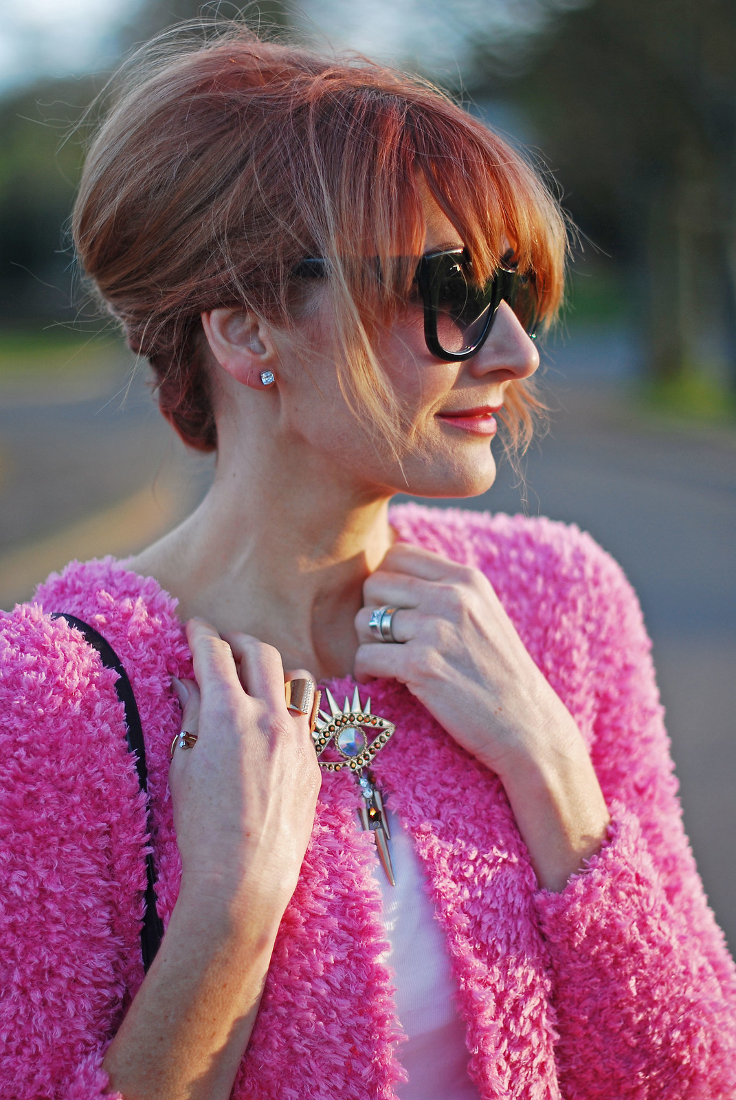 Spring style: Fluffy pink cardigan, up do, cat eye sunglasses, evil eye brooch