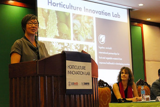 Woman speaking into microphone at podium with Horticulture Innovation Lab insignia IMG_6147eds