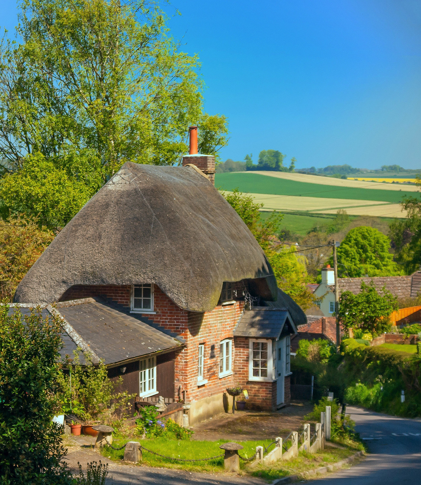 A pretty thatched cottage above the village of Pitton in Wiltshire. Credit Anguskirk
