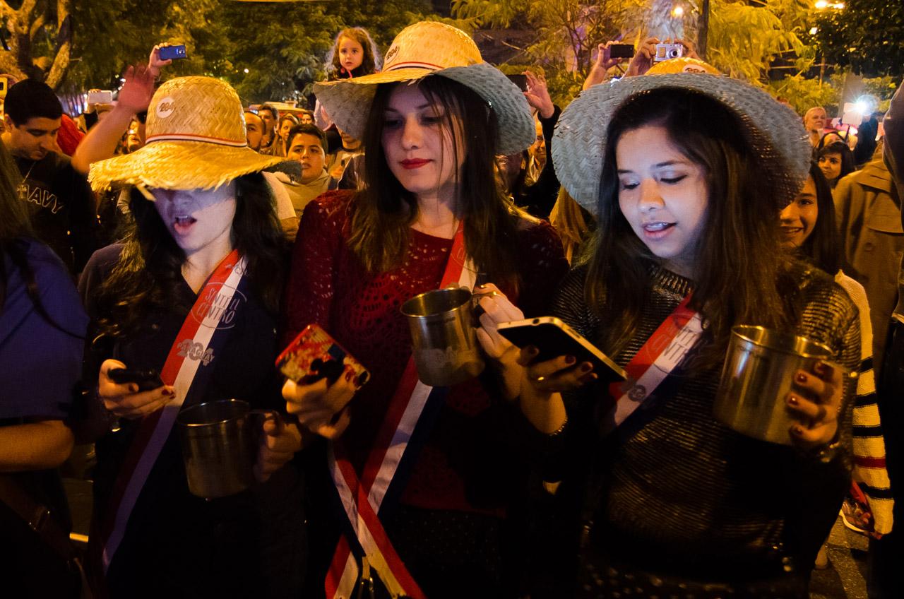Tres señoritas comparten contenido por las redes sociales mientras se lleva a cabo un concierto folklórico en la plaza de armas frente al ex Cabildo de Asunción. (Elton Núñez)