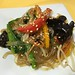 Clear noodles with mung bean sprouts, red and yellow bell peppers, black mushrooms, spinach and sesame seeds