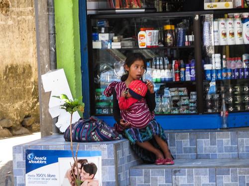 Panajachel: voilà ce qu'elle cachait derrière son dos. Cette petite fille doit en fait s'occuper de son petit frère pendant que leur maman essaie de vendre des étoffes dans la rue.