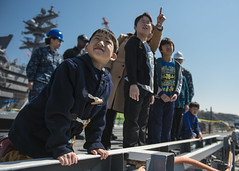 In this file photo, children from the Shunko Gakuen Orphanage look over the side of the USS Ronald Reagan (CVN 76) during a tour of the ship. (U.S. Navy/MC3 Ryan McFarlane)