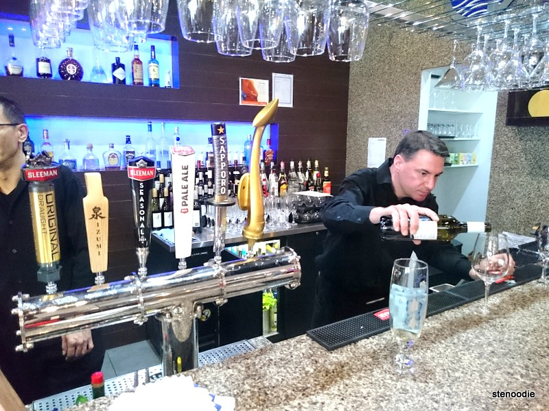 bartender pouring a glass of white wine
