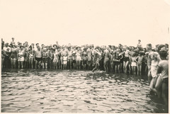 Large group watch two men playing in the water