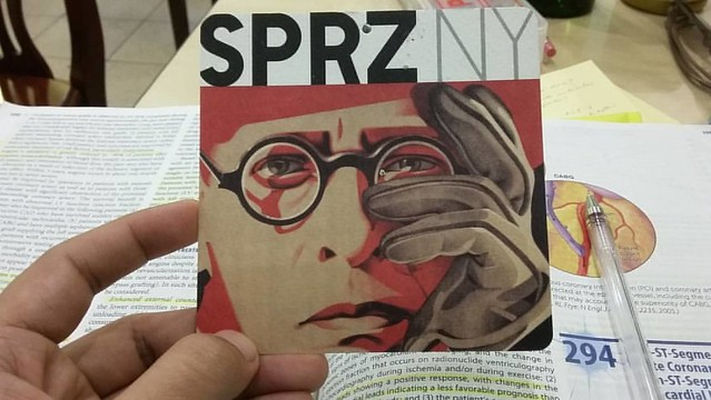 This makeshift bookmark, which I got from a T-shirt tag, features a man with round-shaped glasses. I have the same pair. The man looks confused, and so do I. Haha.