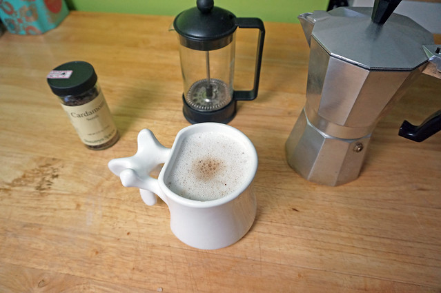Cardamom coffee in a vertebral mug, sitting on a wooden counter along with a jar of cardamom seeds, a French press, and a moka pot
