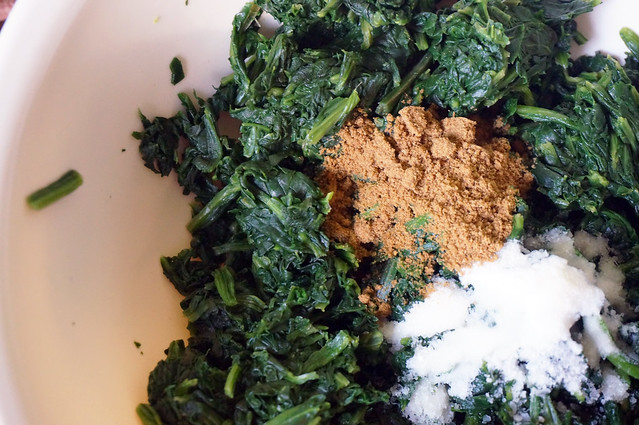 Thawed spinach sits in a ceramic bowl, punctuated by heaps of cumin and salt. Mmmm.