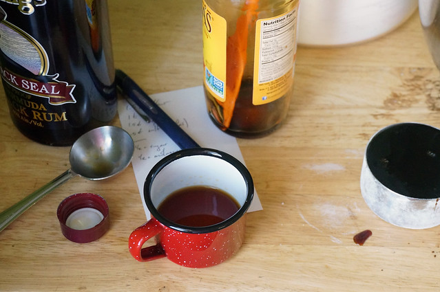 A close-up of the lower portions of bottle of rum and molasses, as well as a tiny enamel cup of rum and a measuring cup brimming with molasses. In the middle of it all, a pen and a notecard with scribbled measurements