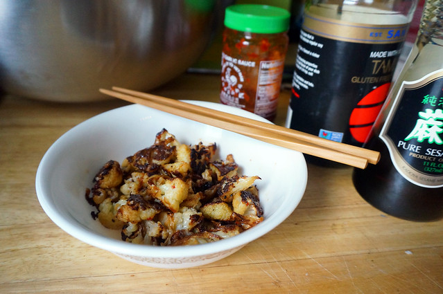 Spicy roasted cauliflower, chopsticks digging in, and you can see the flavoring agents in bottles behind: chile paste, soy sauce, sesame oil