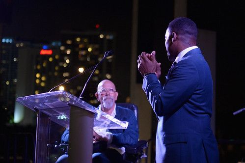 Artist Chuck Close on stage with Franklin Sirmans at PAMM Art of the Party