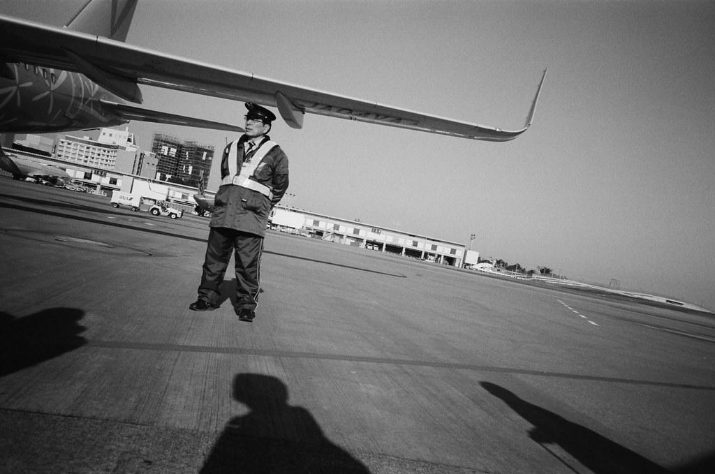 成田機場第三航站 Narita Air Port, Japan / Kodak TRI-X 400 / Lomo LC-A+ 2016/01/31 到了成田機場後改搭國內線的香草航空繼續前往札幌,在停機坪上準備走上飛機時偷拍一張地勤人員的照片。  出發的時候裝了一捲黑白底片,在我印象中往返東京與台北這段行程還沒有用黑白的影像紀錄。  Lomo LC-A+ Kodak TRI-X 400 / 400TX 8561-0027 Photo by Toomore