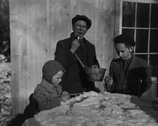 People tasting maple taffy at a sugar bush / Personnes mangeant de la tire dans une érablière