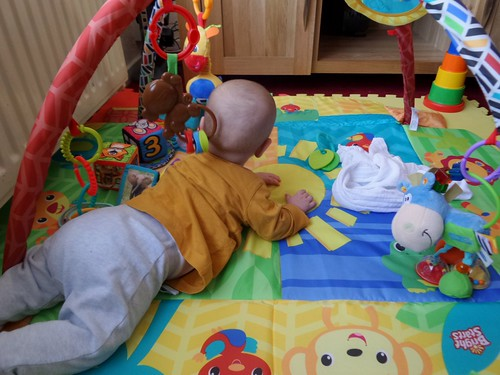 baby in blue trousers and a yellow top, lying on his front on a brightly coloured play mat