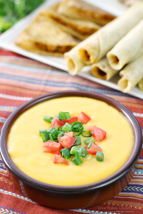 Basic Cheese Sauce in a brown bowl with a stack of taquitos on a plate.