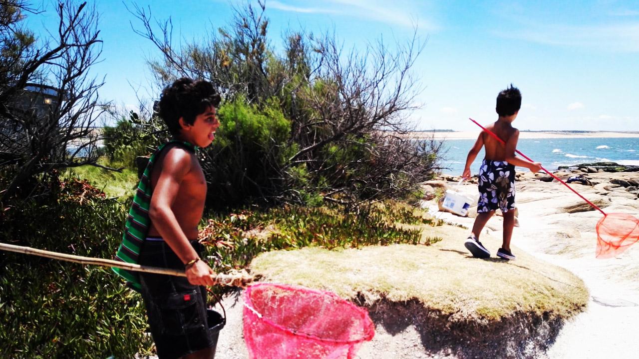 Un par de niños se divierten recolectando pequeños peces atrapados en charcos de agua en la playa de Cabo Polonio. (Fotografía tomada con un smartphone Huawei P8, Elton Núñez)