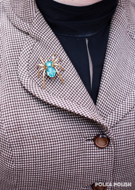 Vintage aqua rhinestone spider brooch on the lapel of a brown checked I. Magnin jacket
