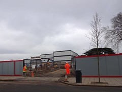 A boarded-off construction site with an open gate in the centre, through which some light gray portacabins can be seen.  A couple of construction workers in high-vis clothing are in the foreground.
