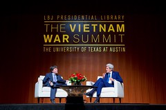 U.S. Secretary of State John Kerry speaks with historian and filmmaker Ken Burns -- who is about to release an 18-hour retrospective about the Vietnam War -- about the past and future of the U.S.-Vietnam relationship while addressing the audience at the Vietnam War Summit held on April 27, 2016, at the LBJ Presidential Library at the University of Texas at Austin. [State Department photo/ Public Domain]