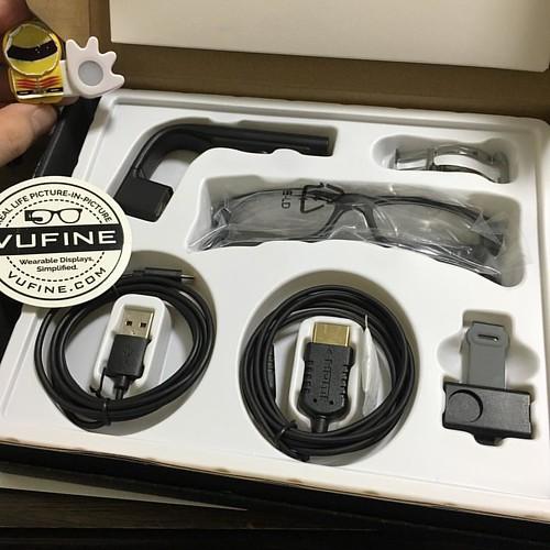 左上から右に、Vufine本体、細いメガネフレーム用のスタビライザ、度なしメガネ、充電用USBケーブル、映像用HDMIケーブル、本体とメガネをくっつける磁石式ドッキングステーション。