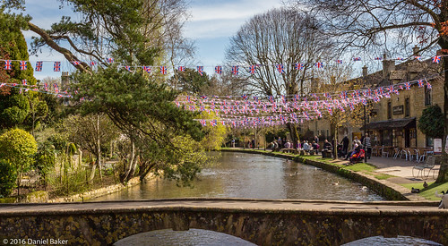 A view from a bride in Bourton-on-the-water with Union Jack bunting over a river