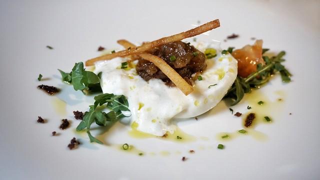 Ensalada de queso burrata con polvo de aceituna negra, virutas de tomate y rúcula silvestre