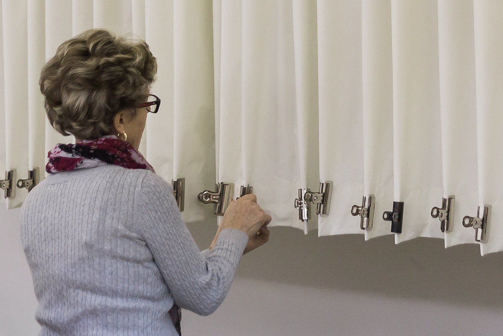 seamstress putting clips on custom draperies in workroom