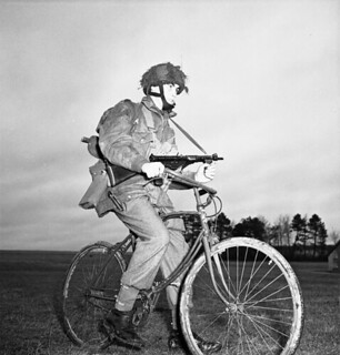 Private Tom J. Phelan, 1st Canadian Parachute Battalion rides his airborne folding bicycle... / Le soldat Tom J. Phelan, du 1er Bataillon canadien de parachutistes, circule sur sa bicyclette pliante aéroportée...