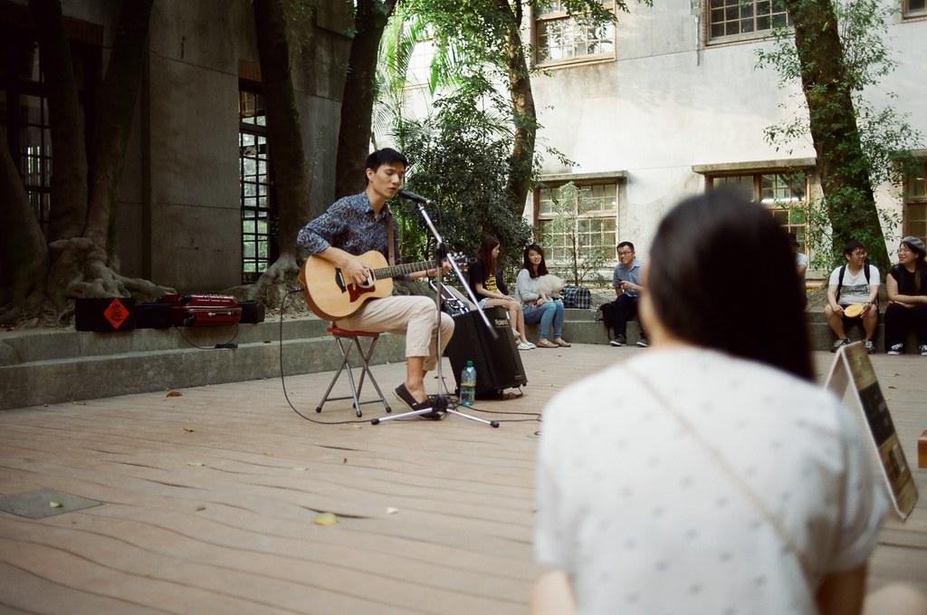 華山文創園區 / KODAK 50D 5203 / Nikon FM2 彈吉他的男孩不時一直望著這女孩,應該是女朋友之類的吧!後來注意到那女孩拿著手機在錄音,幫他紀錄街頭演唱。  Nikon FM2 Nikon AI AF Nikkor 35mm F/2D KODAK 50D 5203 V3 3165-0011 2015/11/07 Photo by Toomore