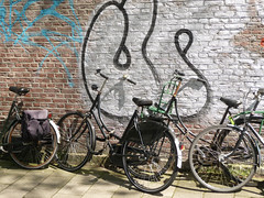 2015.05 - Amsterdam photo: Bikes talking to the tags on the wall, at the Weesperstraat - geotagged free urban picture, in public domain / Commons; Dutch city photography, Fons Heijnsbroek, The Netherlands
