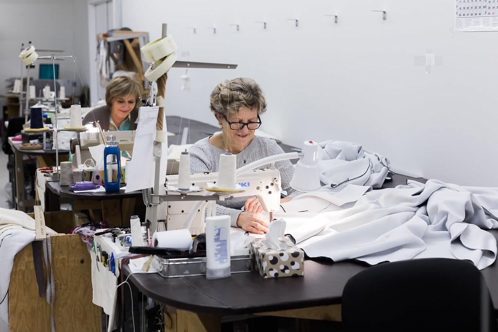 seamstresses sewing custom draperies in workroom