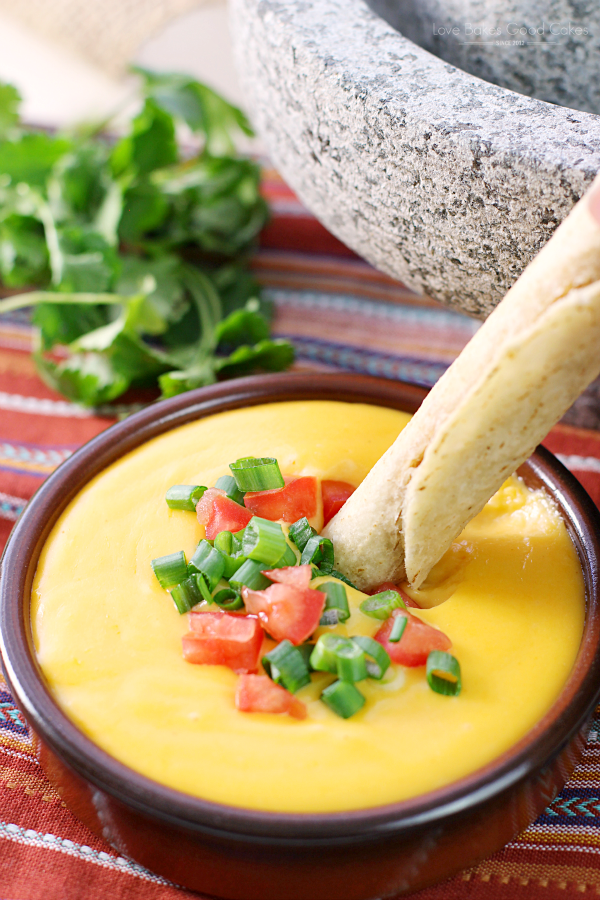 Basic Cheese Sauce in a bowl with a taquito being dipped in the sauce.