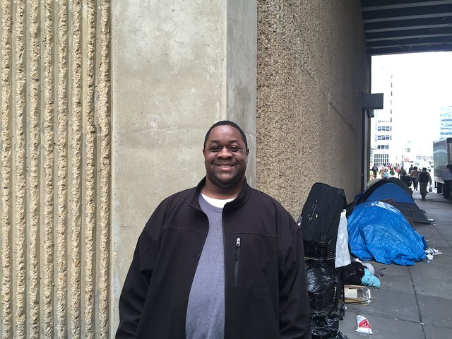 Photo of a man standing on the sidewalk under an underpass. He is smiling. Tents and pedestrians are visible down the stretch of sidewalk behind him.