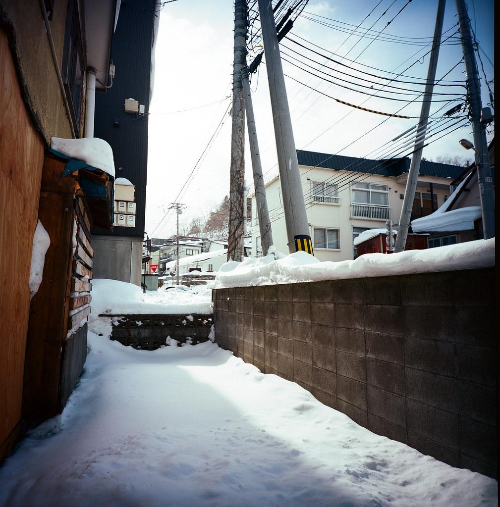 小樽 Otaru 北海道 / Kodak Pro Ektar / Lomo LC-A 120 2016/02/02 從一個巷子走出來,剛好在一個陰影的交接處,我蹲下來看一下觀景窗的構圖,就輕鬆的按下快門。  當我準備要站起來的時候,從上面掉下來一疊厚厚的積雪,沉沉的在我面前落下。  我抖了一下!  一走出小樽車站後我沒有像其他的觀光客一樣往運河的方向前進,反而是左轉經過一個魚市場後往後往山的方向上去,一方面我想看看這裡下雪與住宅區的景色,另一方面總覺得這裡好像有什麼東西等著我去發現。   Lomo LC-A 120 Kodak Pro Ektar 100 120 8279-0005 Photo by Toomore
