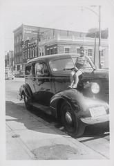 Little boy sitting on the hood of a car