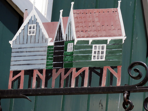 A decorative sign showing off the typical green houses wooden houses in Marken, Holland
