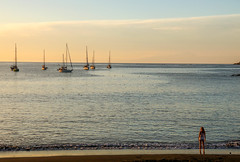 Girl looking at the sailboats from the beach in  Arguineguin