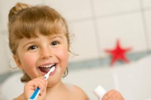 fetita foloseste periuta dentara