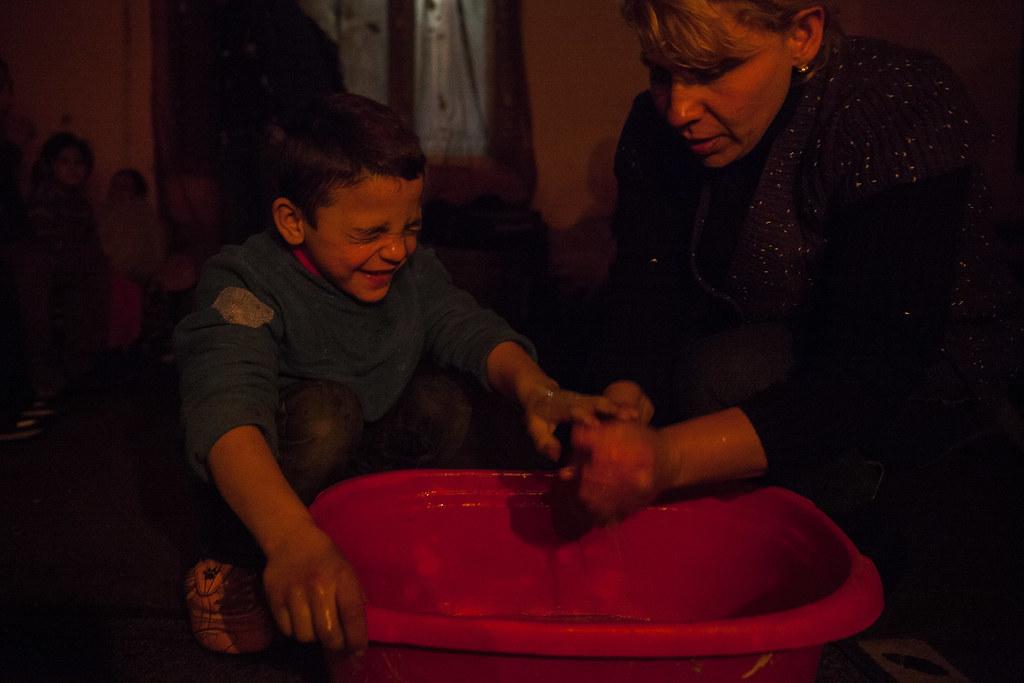 Terike egyik kisebbik fiának mosdatásához áll neki lefekvés előtt. Van olyan ház, legálisan van áram és a családfő hat hónapja köttette vissza, azt mondja, előtte pár hétig nem volt a hátralék miatt, de még azelőtt rendezte a tartozást, mielőtt leszerelték volna az órát. Most havi 3800 forintból jön ki a villanyszámla. A szobában forróság van - alaposan bedurrantottak a kályhába - mert fürdetni készülnek a kisgyerekeket. 11-en laknak itt a gyerekekkel és a nagyapával együtt. Nemrég kaptak fát is segélyként, egy köbmétert. Ezzel 2-3 hétig tudnak fűteni. | Fotó: Magócsi Márton