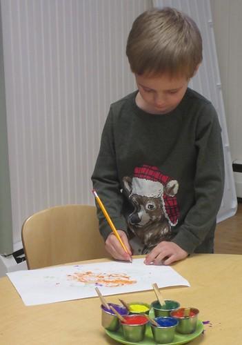 signing his artwork