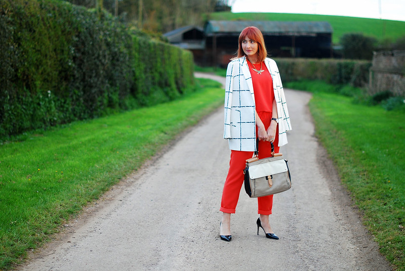 SS16: Orange short sleeved jumpsuit, black and white window pane check jacket, black pointed toe heels, Aztec-style eagle necklace, colour block bag | Not Dressed As Lamb