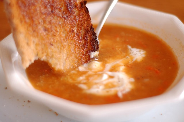 Dipping toasted peasant bread in the red lentil soup with chili paste and lemon by Eve Fox, the Garden of Eating, copyright 2015