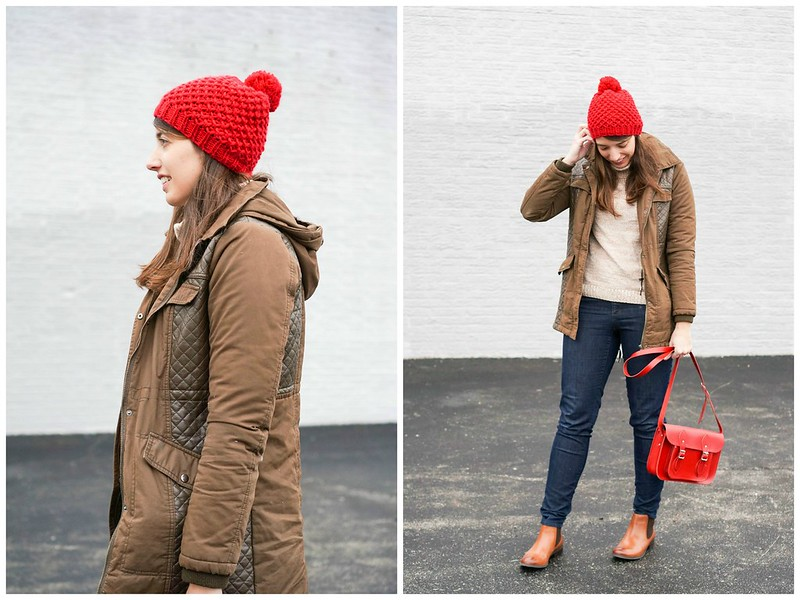 red hat + green winter coat + tan turtleneck sweater + red purse + jeans