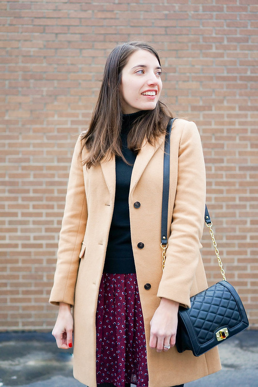 camel wool coat + black quilted crossbody purse + black turtleneck + floral print skirt; winter work outfit