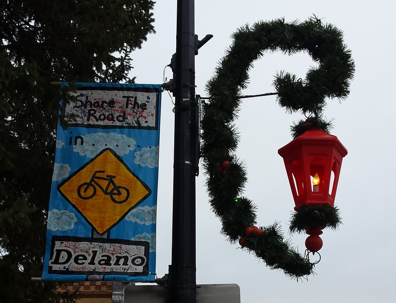 Share the Road with Bicycles banner next to a streetlight hanging from garland