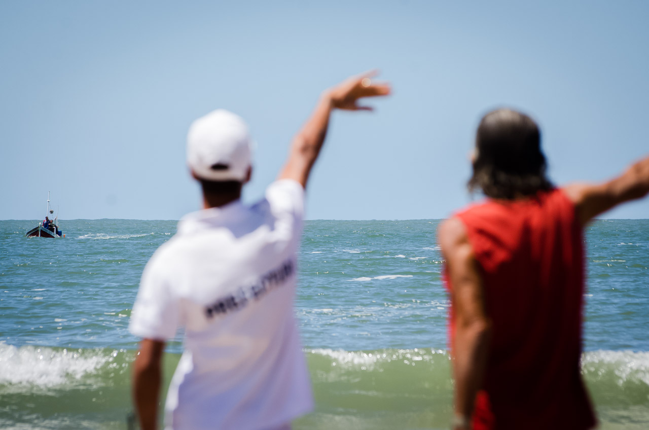 Un funcionario de la prefectura naval y un pescador dirigen a los marineros que se aproximan a la costa a bordo de un barco pesquero, desde la Playa del Rivero, en Punta del Diablo. (Elton Núñez)