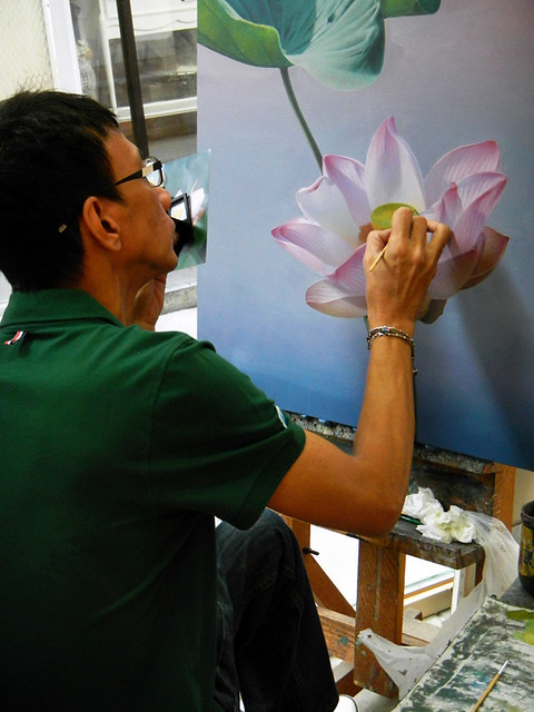 A Thai artist painting a pink lotus in Bangkok