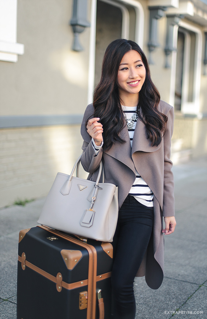 travel outfit wrap jacket black jeans dvf trunk suitcase