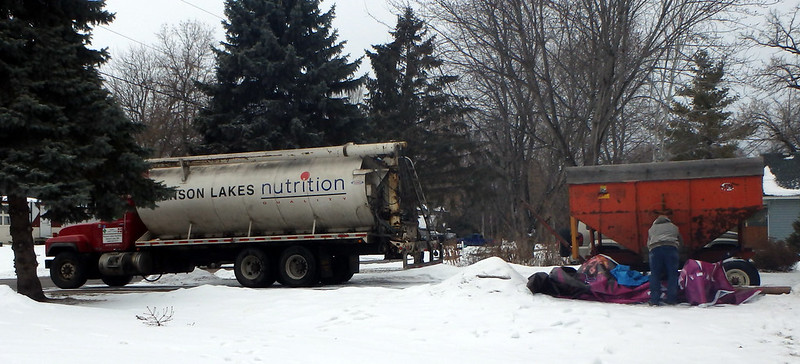 Munson Lake Nutrition truck and a man standing next to a large red bin